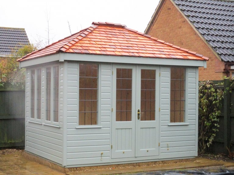 2.4 x 3.0m Cley Summerhouse with cedar shingle tiles on the roof and painted in Exterior Sage