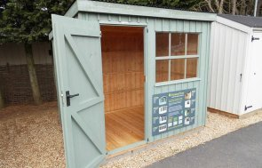 Oxburgh Shed with open door measuring 1.8 x 2.4m painted in Terrace Green at our Burford Show Centre