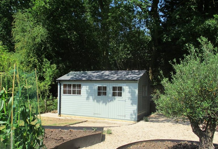 3.0 x 4.8m Shiplap Clad Superior Shed painted in Exterior Sage, with grey slate effect roof tiles