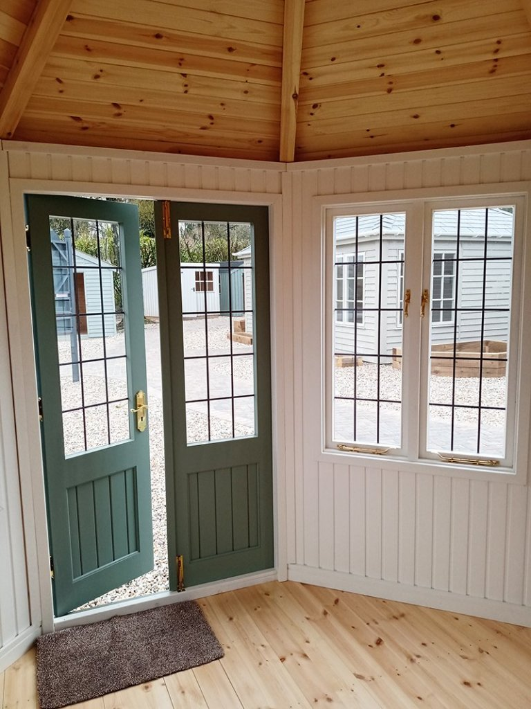 Inside Sevenoaks' 3.0 x 3.0m Wiveton Summerhouse in Exterior Sage Paint with Ivory painted matchboard walls and a natural lacquered floor