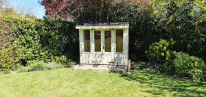 1.8 x 2.4m Flatford National Trust Summerhouse painted in Dome Ochre with traditional design features including corrugated sheeting on the roof and leaded windows