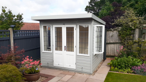 2.4 x 2.4m Thornham Summerhouse painted in Exterior Pebble & Ivory with leaded windows and shiplap cladding