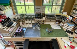 Aircraft scale modelling setup inside a 1.8 x 2.4m Superior Shed with a wide selection of paints displayed on an L-Shaped Workbench