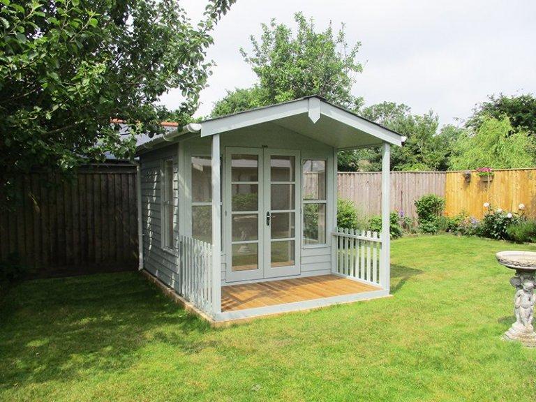 2.4 x 3.6m Morston Summerhouse painted in Exterior Verdigris with apex roof design and veranda