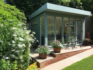 2.4 x 3.6m Salthouse Studio painted in Exterior Sage with interior furnished with rattan table and chairs