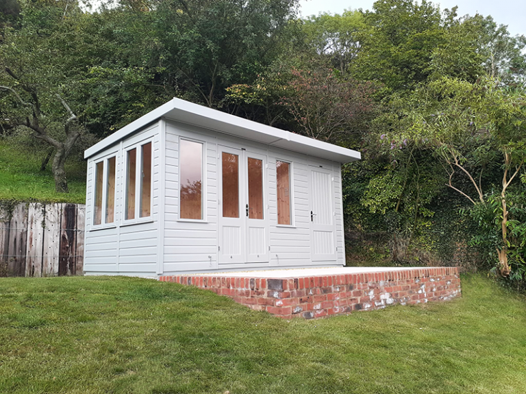 2.4 x 4.2m Thornham Summerhouse with storage partition painted in Exterior Verdigris with stylish pent roof design
